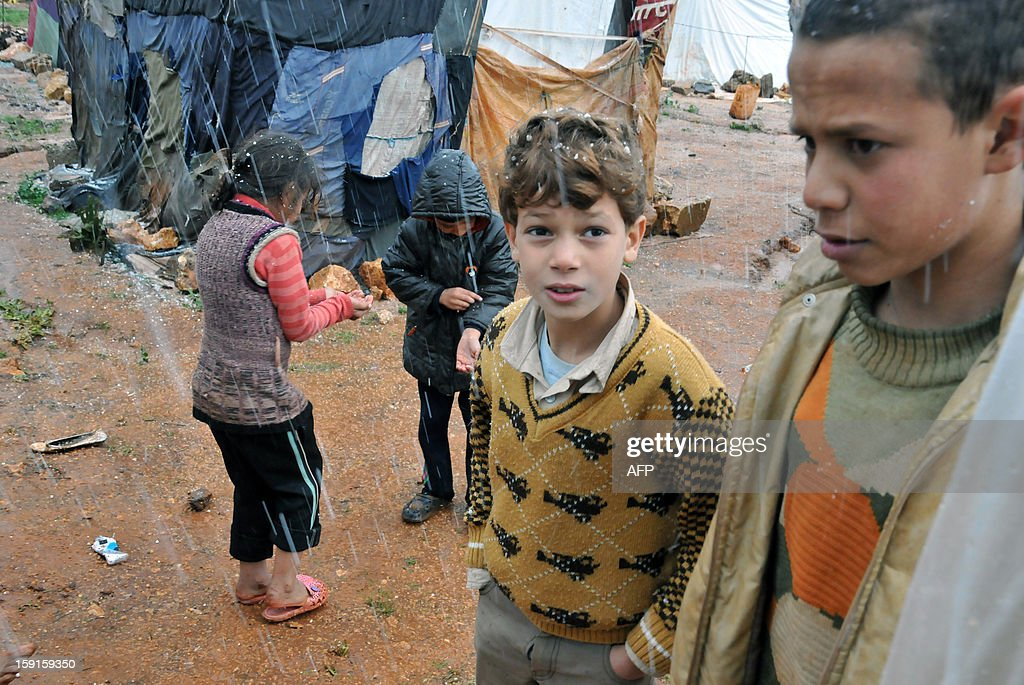 Bedouin children from Syria, who have taken refuge with their families for the winter in Lebanon, stand in the sleet at their camp close to the village of Kfarkahel, in the Koura district near the northern city of Tripoli on January 9, 2013, as stormy weather sparked widespread flooding, prompting chaos on the roads and a nationwide school closure. The number of Syrian refugees in Lebanon is already totaling 156,000, according to UN figures, and 200,000 according to the Lebanese government estimates.