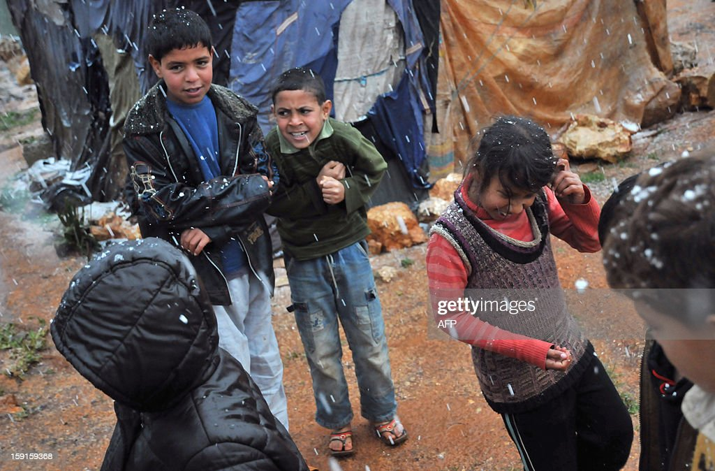 Bedouin children from Syria, who have taken refuge with their families for the winter in Lebanon, play under the sleet at their camp close to the village of Kfarkahel, in the Koura district near the northern city of Tripoli on January 9, 2013, as stormy weather sparked widespread flooding, prompting chaos on the roads and a nationwide school closure. The number of Syrian refugees in Lebanon is already totaling 156,000, according to UN figures, and 200,000 according to the Lebanese government estimates. AFP PHOTO/IBRAHIM CHALHOUB