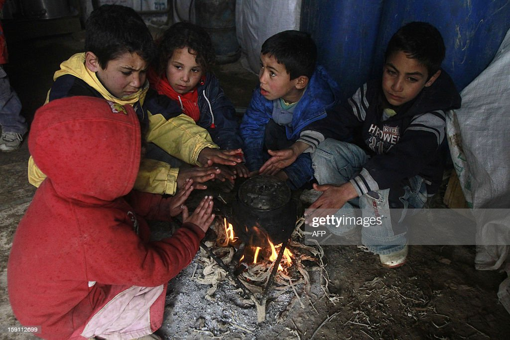 Bedouin children from the al-Rashaida tribe warm themselves on a fire under a tent at their camp in the desert south of the West Bank city of Bethlehem on January 8, 2013. Stormy weather, including high winds and heavy rainfall, lashed Israel and the Palestinian territories, downing powerlines and trees and causing several injuries.