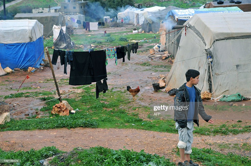Bedouin families from Syria, who have taken refuge for the winter in Lebanon, are seen camped close to the village of Kfarkahel, in the Koura district near the northern city of Tripoli on January 9, 2013, as stormy weather sparked widespread flooding, prompting chaos on the roads and a nationwide school closure. The number of Syrian refugees in Lebanon is already totaling 156,000, according to UN figures, and 200,000 according to the Lebanese government estimates. AFP PHOTO/IBRAHIM CHALHOUB