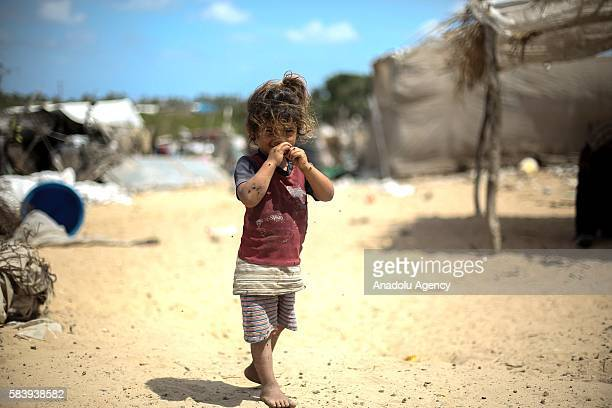 Bedouin girl is seen near the wreckages and their makeshift huts without water and basic living necessities at Khan Younis in Gaza City Gaza on July...