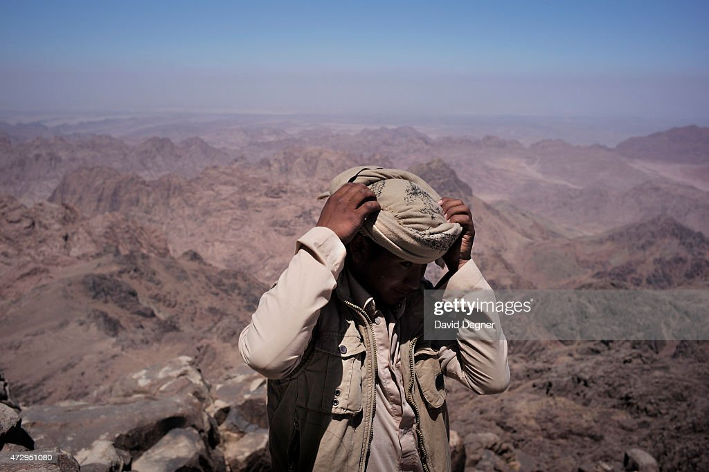 A bedouin guide adjusts his head scarf while on top of Mount Kathrine, he is part of a group leading tourists hiking through the mountains of South Sinai on April 18, 2015 near St. Catherine, Egypt. Bedouins guides in the Sinai peninsula face stiff competition and many Sinai Bedouins are unemployed due to the lack of employment opportunities.
