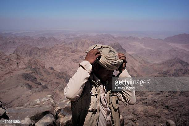 A bedouin guide adjusts his head scarf while on top of Mount Kathrine he is part of a group leading tourists hiking through the mountains of South...
