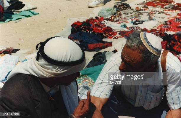 A Bedouin man and a Jewish man bargaining at the Bedouin market in Beersheba