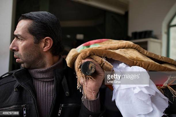 A Bedouin mourner carries the body of Saleh Abu Latif during his funeral on December 25 2013 in Rahat Israel Abu Latif An Israeli security fence...