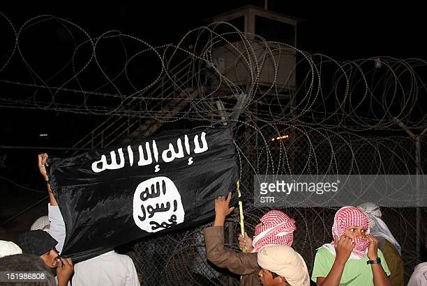 Bedouin protesters wave an AlQaedaaffiliated flag near a watch tower in Egypt's Sinai on September 14 2012 after they stormed a compound of the...