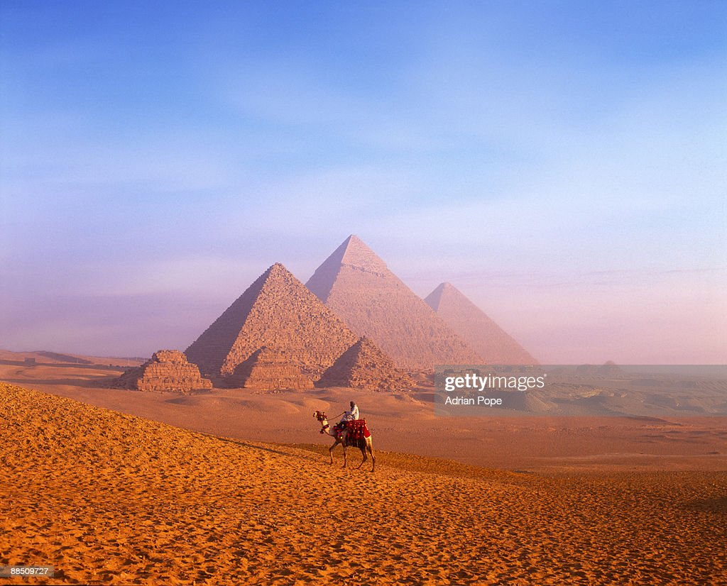 Bedouin tribesman on camel with pyramids beyond
