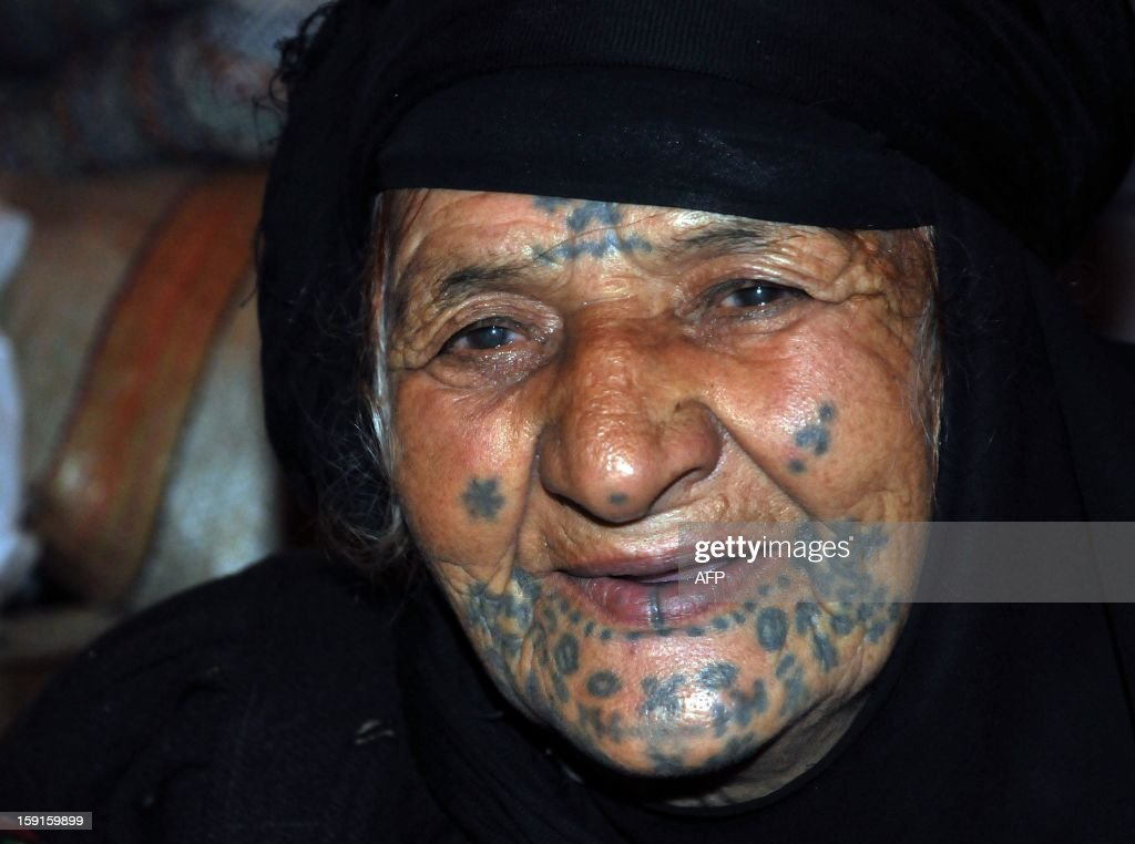 A Bedouin woman from Syria, with her face tattooed, sits in a tent after taking refuge for the winter in neighboring Lebanon, close to the village of Kfarkahel, in the Koura district near the northern city of Tripoli on January 9, 2013. The poked henna tattoos are traditionally tapped on the face and hands of Bedouin women from across the Arabian peninsular, and are mainly for decorative and ornamental purposes, and occasionally at the location of pain or injury.