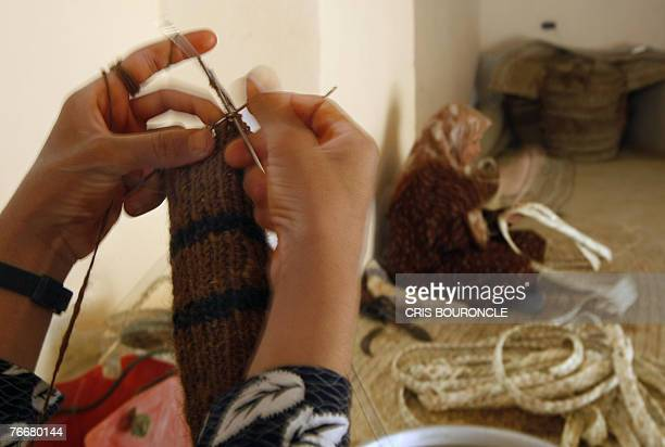 Bedouin woman knits wool socks while another one weaves stripped palm fronds to make mats at the alHayah community cooperative in the ElFarafra Oasis...