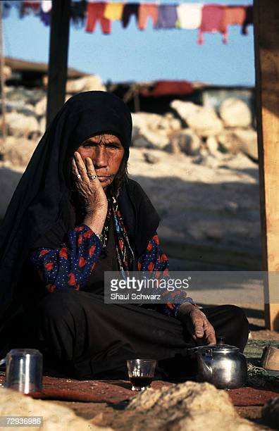 A bedouin woman makes tea in the Negev Desert Israel Bedouins are Arab nomadic pastoralist groups primarily found in the Middle East where they form...