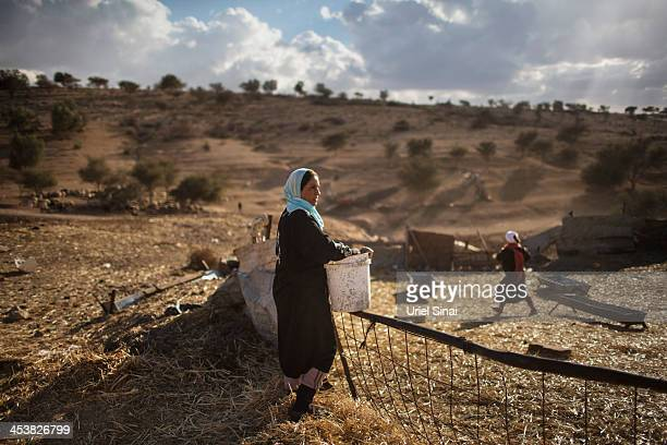 A Bedouin woman of the AlQiyaan tribe stands while working outside her house on December 5 2013 At the Bedouin village of Umm AlHiran Israel Roughly...