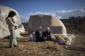 Bedouin women and children of the AlQiyaan tribe spend time aoutside their house on December 5 2013 At the Bedouin village of Umm AlHiran Israel...