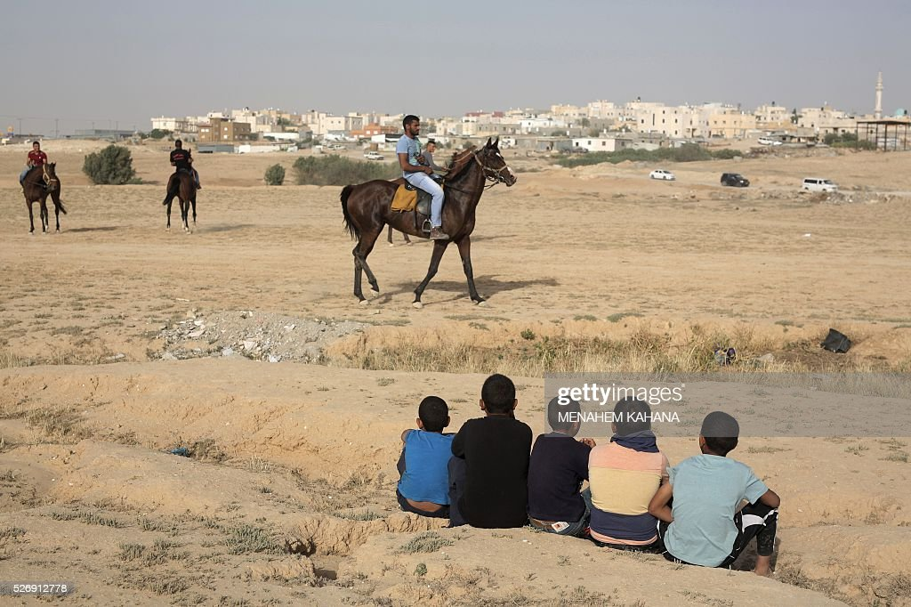 Bedouins ride their horses in the southern Israeli Bedouin town of Ar'arat an-Naqab in the Negev desert on May 1, 2016. / AFP / MENAHEM