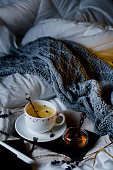 Evening tea in bed with gentle lighting. Tea with lemon and honey on a tray and knit plaid on a white bed