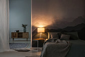 Bedroom interior in the night with warm light of lamp on table near wooden cupboard