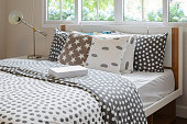 bedroom interior design with polka dot pillows on bed and decorative bedside table lamp.