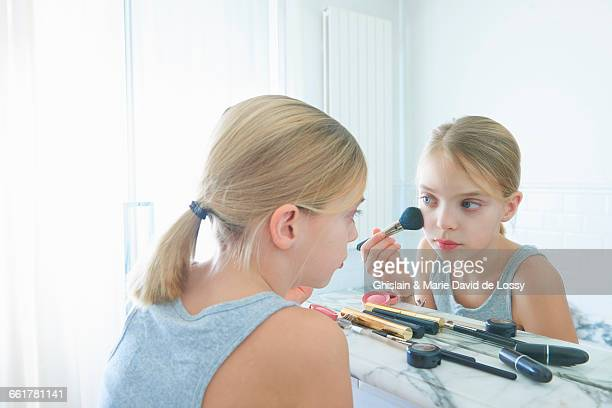 Bedroom mirror image of girl applying blusher