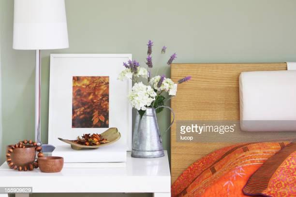Quarto mesa de cabeceira com luzes de decoração e flores
