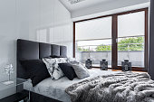 Modern bedroom with double bed, high gloss wall and big window