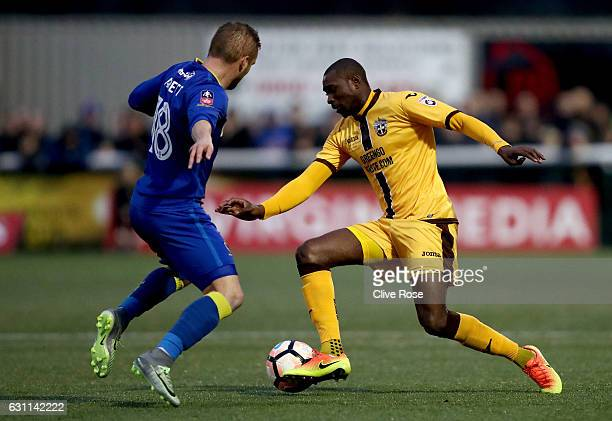 Bedsente Gomis of Sutton United and Dean Parrett of AFC Wimbledon compete for the ball during The Emirates FA Cup Third Round match between Sutton...