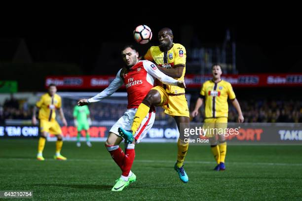 Bedsente Gomis of Sutton United battles for the ball with Lucas of Arsenal during the Emirates FA Cup fifth round match between Sutton United and...