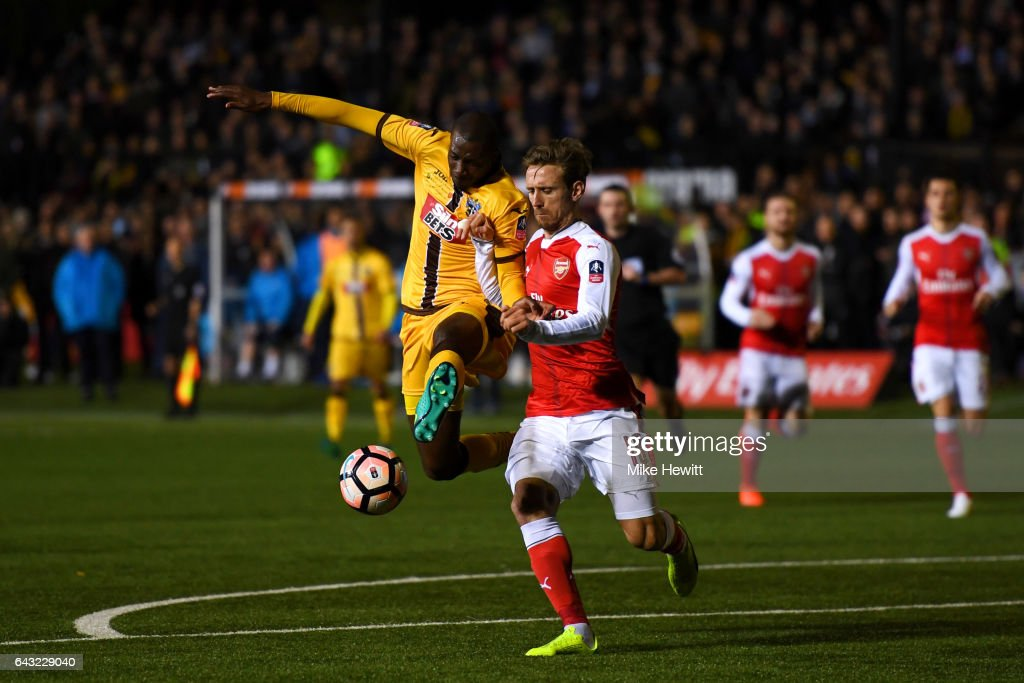 Bedsente Gomis of Sutton United battles for the ball with Nacho Monreal of Arsenal during the Emirates FA Cup fifth round match between Sutton United and Arsenal on February 20, 2017 in Sutton, Greater London.