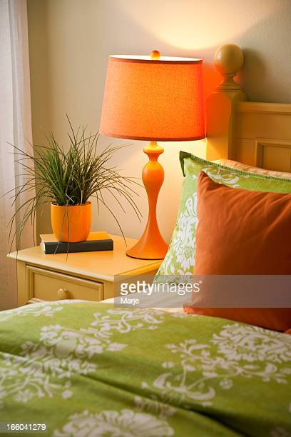 A bedside next to a bed with green covers