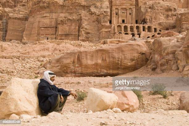 Beduin smoking a cigarette sitting on the ground of the ancient city of Petra