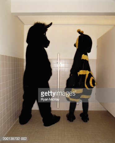 Bee and bull having conversation while at  urinal, rear view : Stock Photo