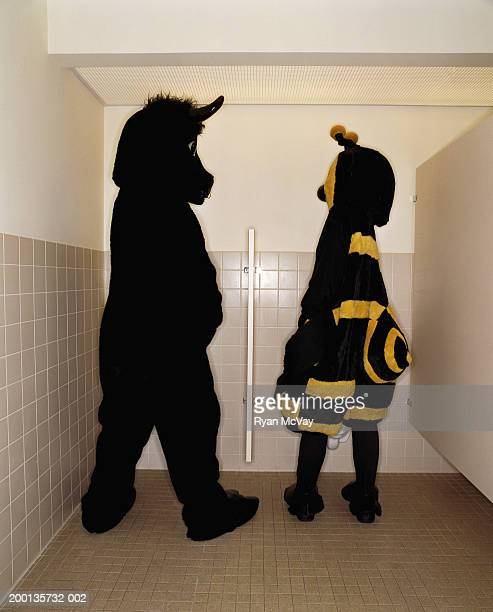 Bee and bull having conversation while at  urinal, rear view