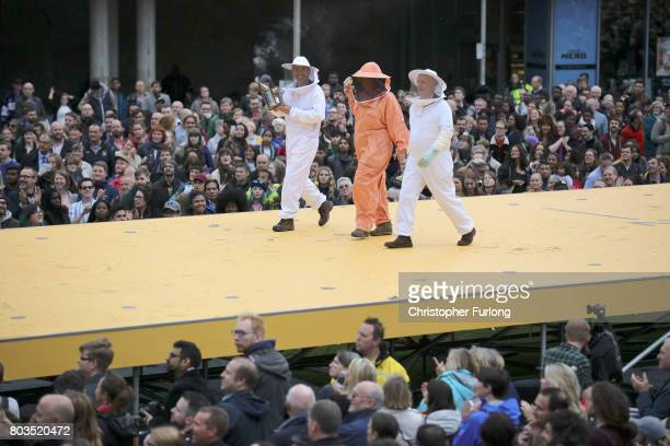 Bee keepers parade on a 100m long catwalk installed high above the ground as part of What Is The City But The People show in Piccadilly Gardens on...