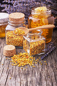Golden bee pollen in small glass jars with honey comb on the texture wooden background with the wooden spoon. Concept of healthy food. selective Focus