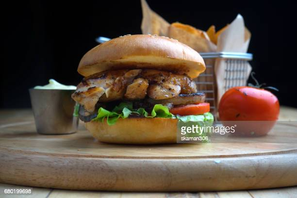 Beef and Cheese Burger with chip and tomatoes on wooden plate