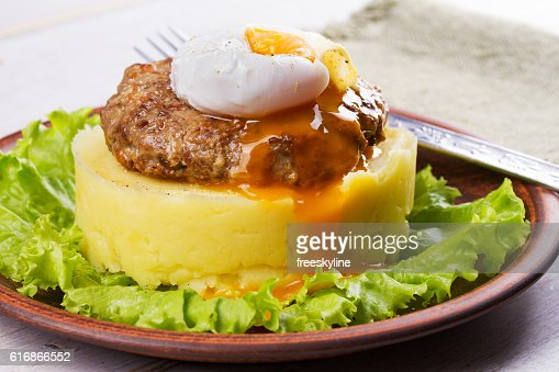 Beef and pork patty with poached egg and smashed potato : Stock Photo