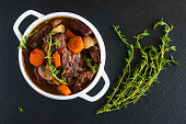 Beef Bourguignon in a white soup bowl on black stone background, top view. Stew with carrots, onions, mushrooms, bacon, garlic and bouquet garni. The dish is served with fresh thyme.