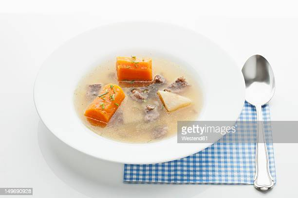 Beef broth in plate on white background
