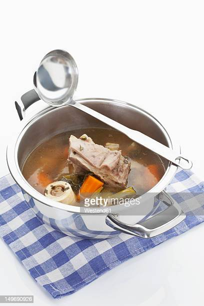 Beef broth in stew pot with ladle