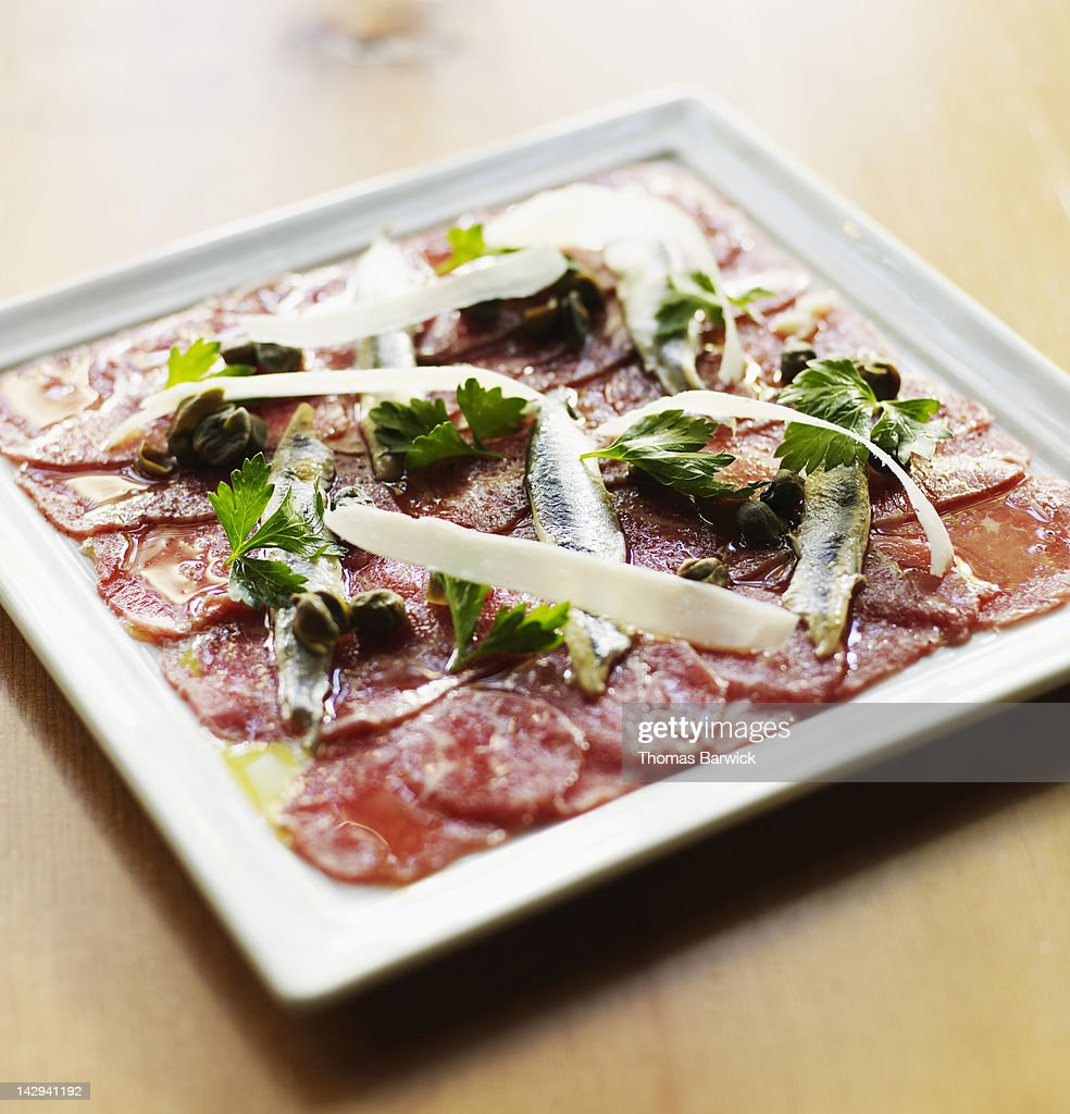 Beef carpaccio, reggiano, olive oil and anchovies : Stock Photo