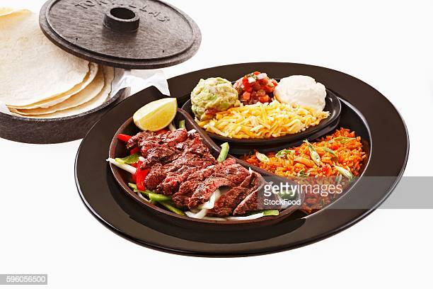 Beef fajita with accompaniments and tortillas