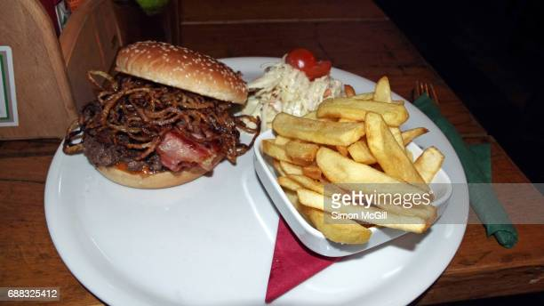 Beef hamburger with bacon and fried onion rings, served with potato chips and coleslaw at a pub in Prague, Czech Republic