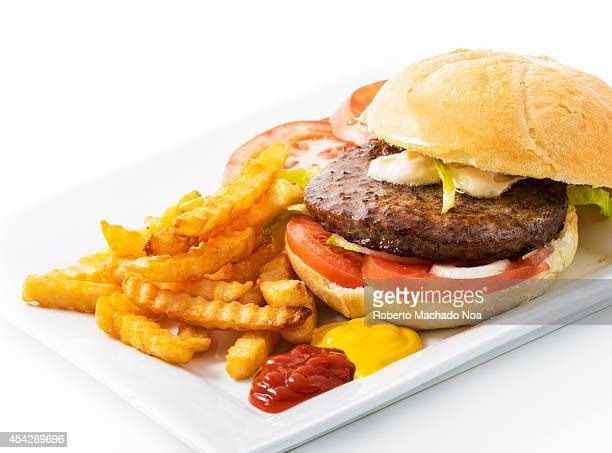 Beef hamburguer in white bread served with french frieslettucetomatoonionsfrench friesketchupmayonnaise and mustard