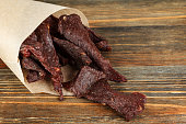 Beef jerky on a wooden board close-up