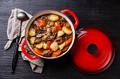 Beef meat stew pot with potatoes, carrots and spices in cast iron pan on burned black wooden background