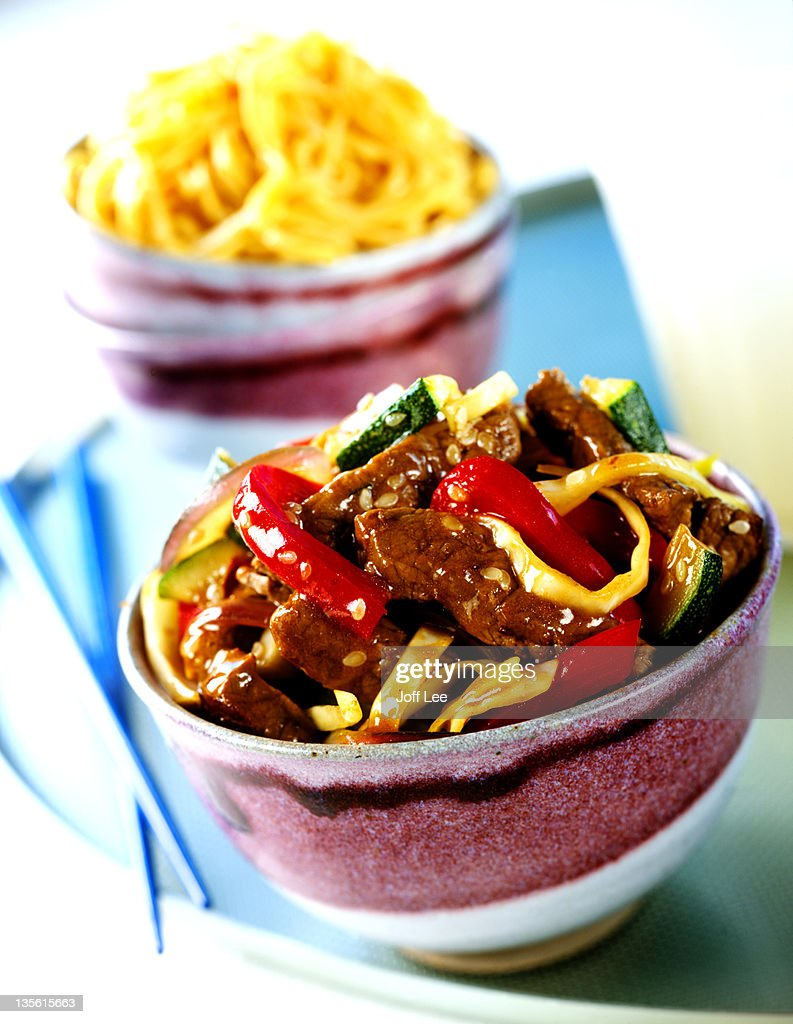 Beef & noodle stir-fry in bowl with chopsticks : Stock Photo