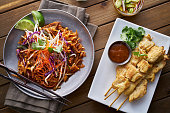 beef pad thai and chicken satay dinner viewed from above in flat lay composition
