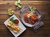 beef pad thai and chicken satay dinner viewed from above on wooden table
