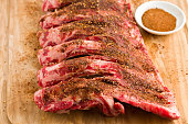 """A high angle view of a slab of beef ribs with a bowl of spicy,Texas style dry rub lying on a wooden cutting board."""