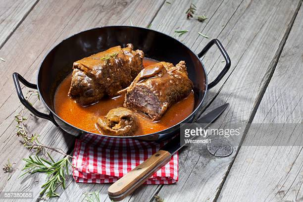 Beef roulades in braising pan, rosmary, kitchen towel and knife on wood