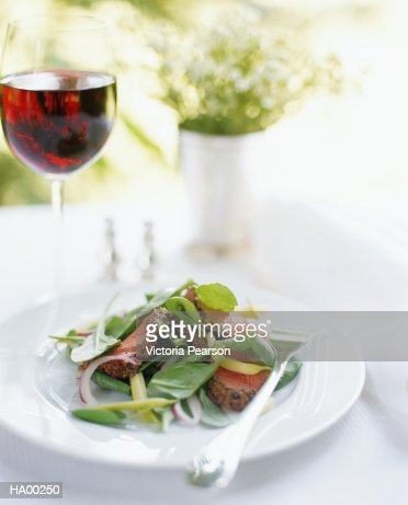 Beef salad on plate beside glass of red wine : Stock Photo
