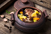 baked beef meat with orange sauce in a rustic pot